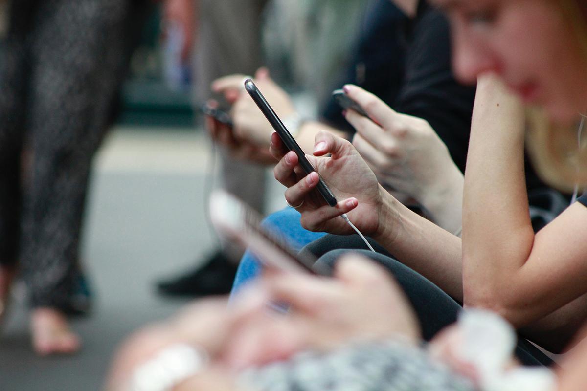 Personer sitter och tittar i telefoner