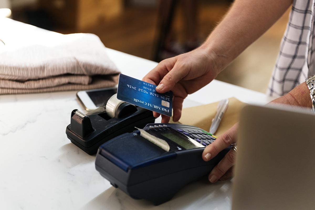 Person betalar med kort i en kortläsare
