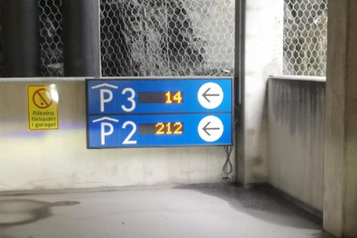 Parkeringskyltar i ett garage visar hur parkeringssystemet fungerar