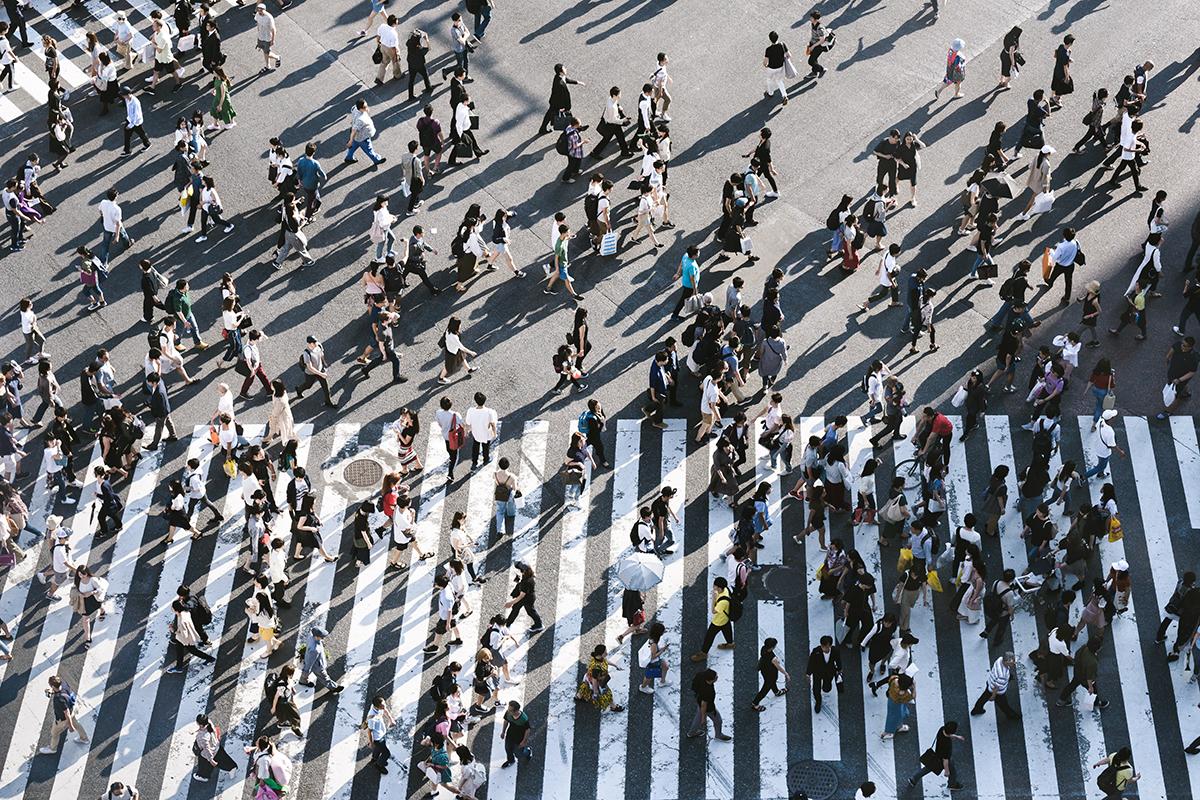 Folkmassa går över en gata